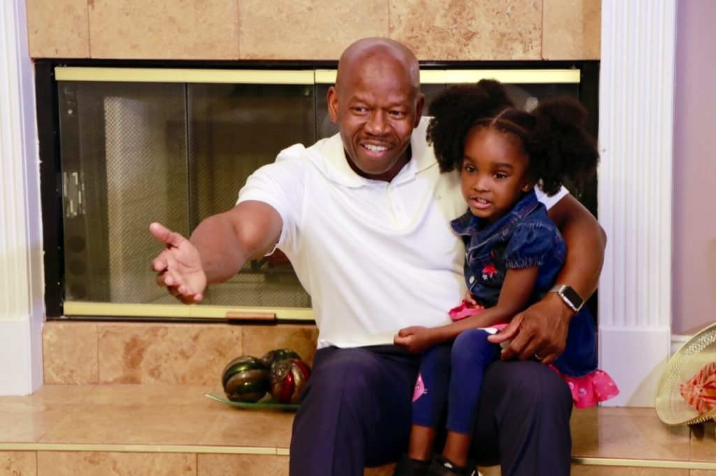 Carson Tranquille with his daughter by the fireplace.